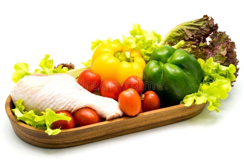 Rå höna och grönsaker i trämagasin arkivfoto