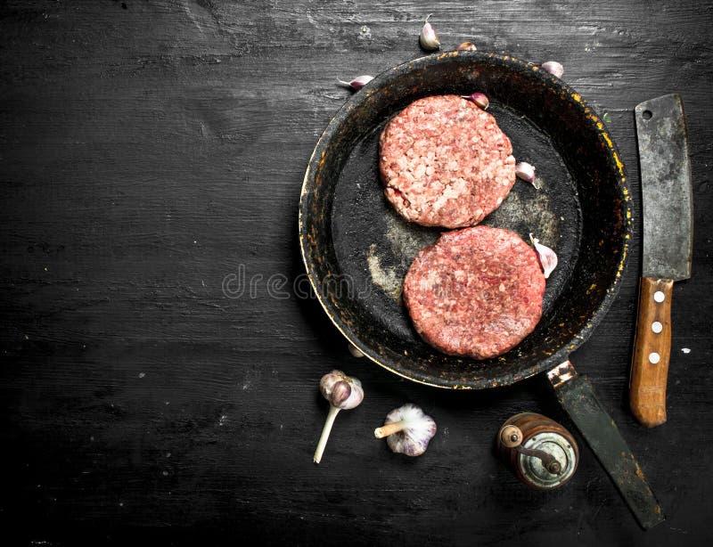 Rå hamburgare från nötkött i en gammal stekpanna med vitlök och kryddor fotografering för bildbyråer