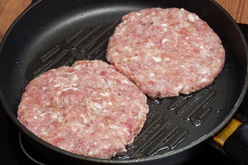 Rå hamburgarekotletter eller hamburgaresmå pastejer på stekpannan arkivfoto