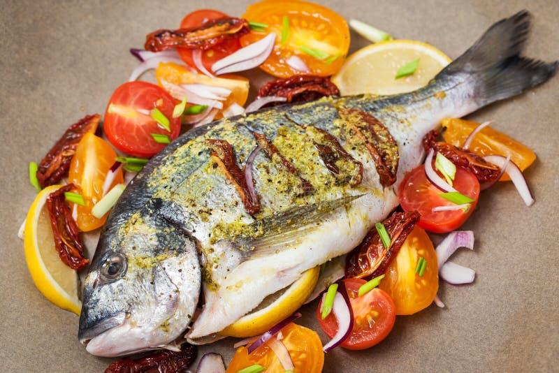 Rå hel fisk för havsbraxen och grönsakingredienser royaltyfria bilder