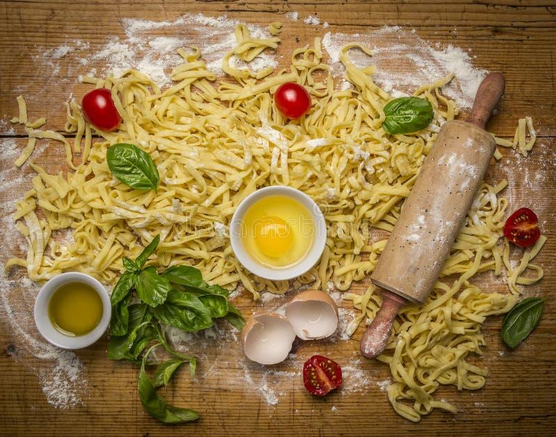 Rå hemlagad pasta med ingredienser för pasta, tomater, mjöl, kavel, ägg och olivolja på lantlig träbakgrundsöverkant VI royaltyfri foto