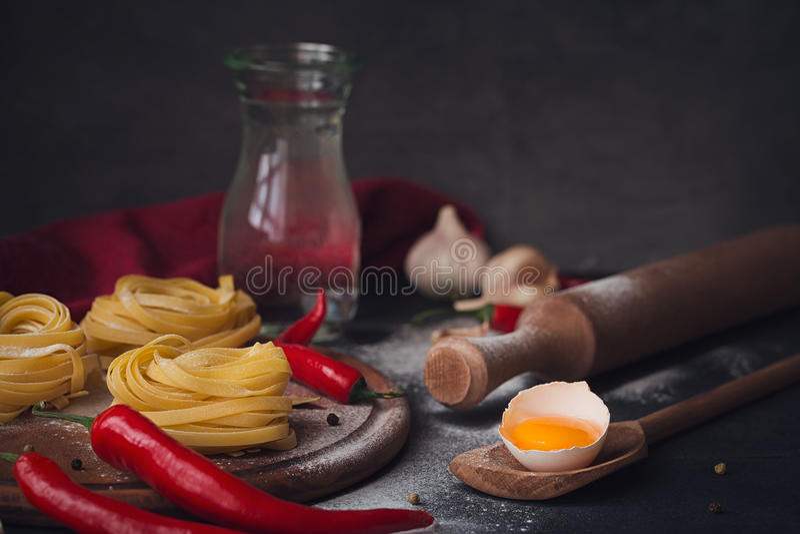 Rå hemlagad pasta med mjöl och kryddor på den lantliga backgrounen fotografering för bildbyråer