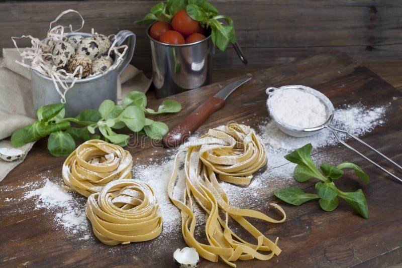 Rå hemlagad pasta, vakteleaster ägg i en aluminum kopp, grön grönsallat, tomater och mjöl på trätabellen royaltyfri foto