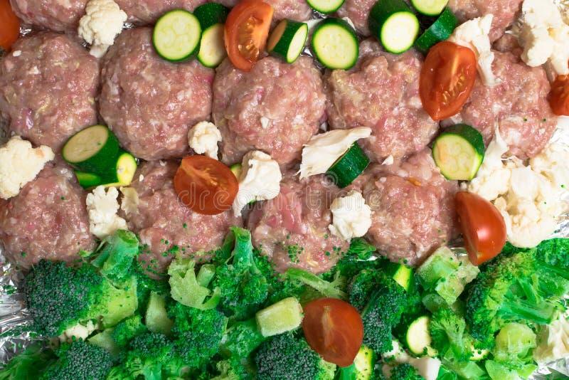 rå hemlagade köttbollar, kotletter med blandningen av grönsaker royaltyfria foton