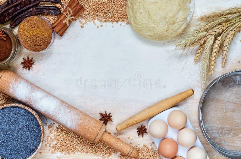Rå igredients för att laga mat bröd- eller kakaägg, kryddor, mjöl, kavel, sikt Stekhet bakgrund med kopieringsutrymme för text arkivbild
