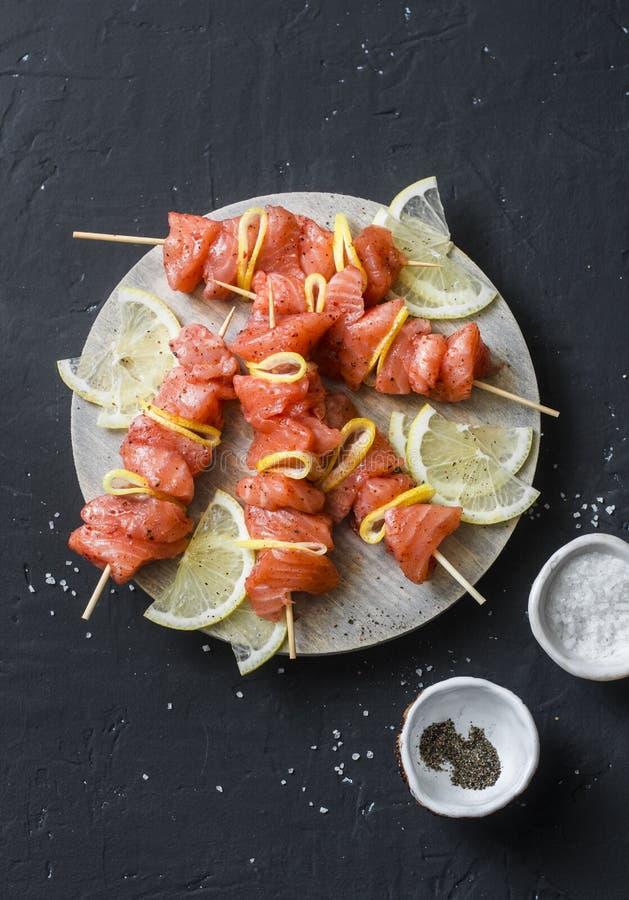 Rå ingredienser för att laga mat laxsteknålar på gallret Rå laxsteknålar, citron, peppar, hav som är salt på en skärbräda på mörk arkivbild