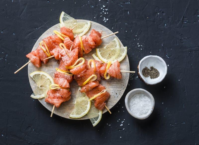 Rå ingredienser för att laga mat laxsteknålar på gallret Rå laxsteknålar, citron, peppar, hav som är salt på en skärbräda på mörk royaltyfria bilder