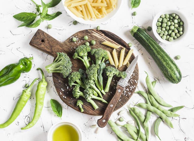 Rå ingredienser för att laga mat vegetarisk lunch - torr pasta, ny broccoli, zucchini, gröna ärtor och bönor, olivolja royaltyfri foto