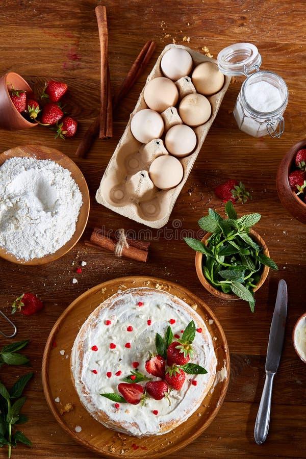 Rå ingredienser för bästa sikt för att laga mat den jordgubbepajen eller kakan på trätabellen, lekmanna- lägenhet Kort med olikt  royaltyfria foton
