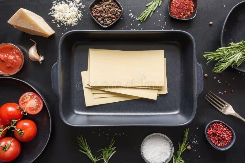 Rå ingredienser för lasagner, pasta, grönsaker och örter på svart kopiera avstånd arkivfoto