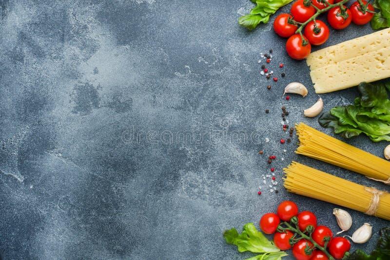 Rå italiensk pastaspagetti och laga mat gräsplaner för ost för körsbärsröda tomater för ingredienser Italienskt matmörker stenar  royaltyfria foton