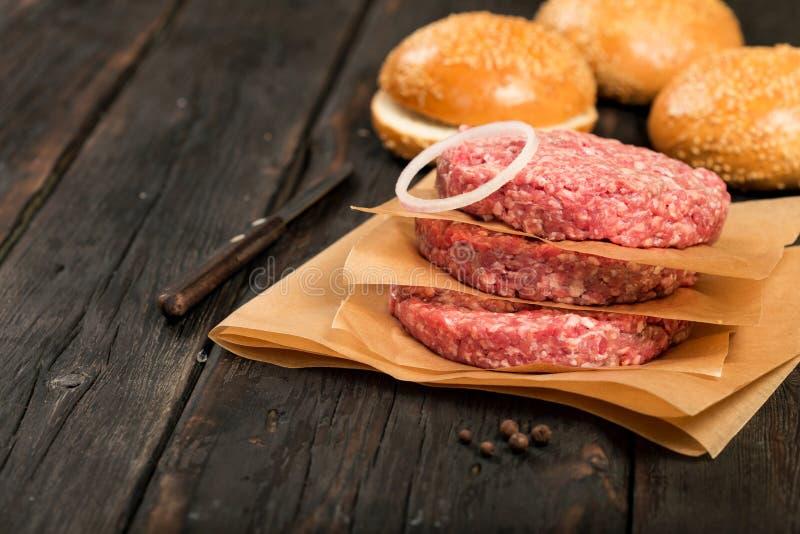 Rå jordkotletter för biff för nötköttkötthamburgare på trätabellen royaltyfria bilder