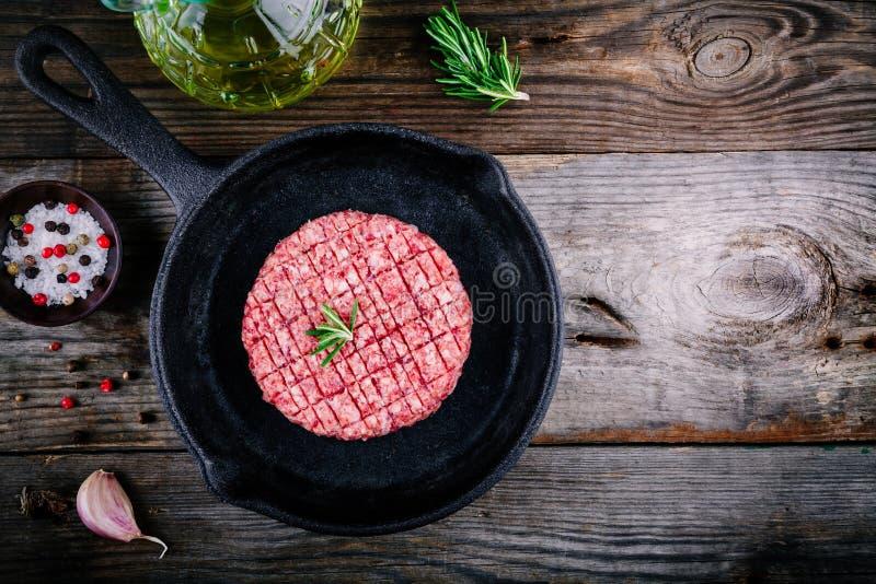 Rå jordkotletter för biff för nötköttkötthamburgare i stekpanna arkivbild