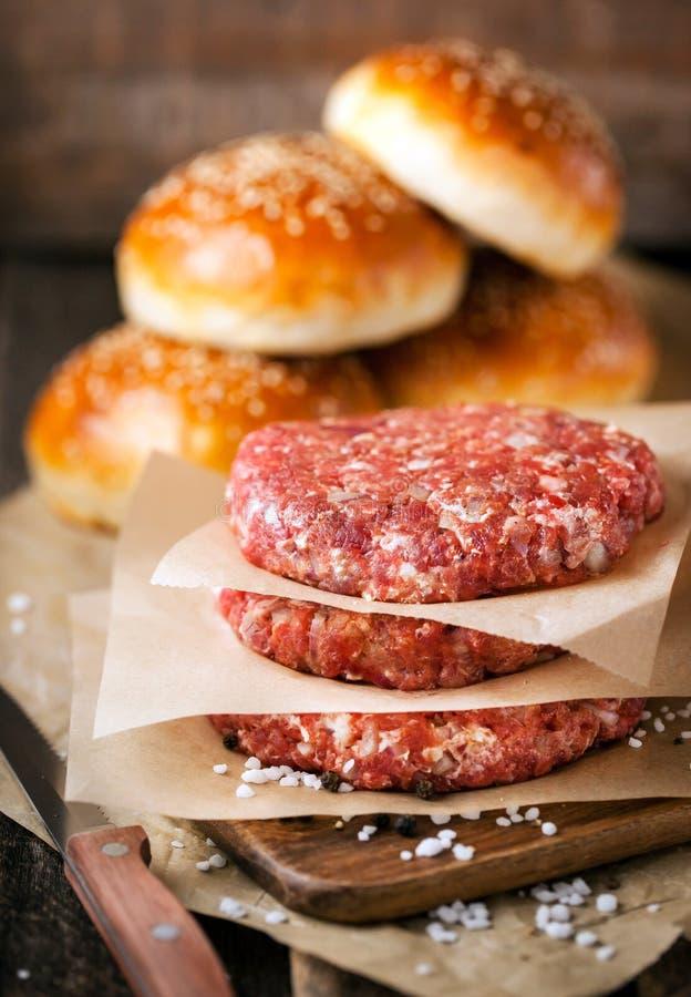 Rå jordkotletter för nötköttköttbiff och hamburgarebullar royaltyfria bilder