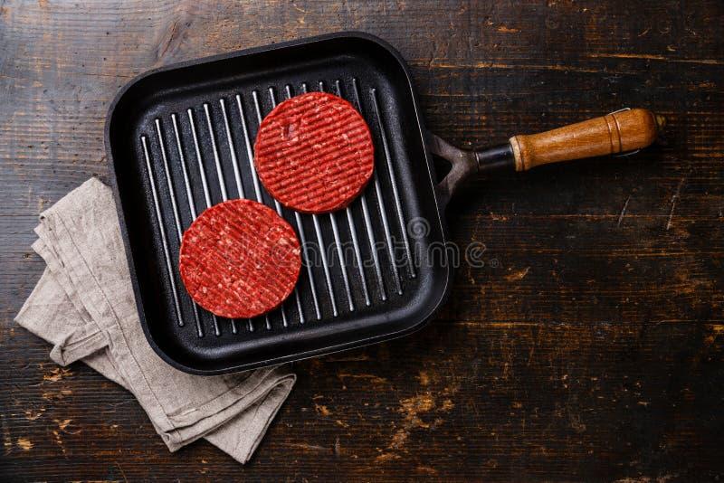 Rå jordkotletter för nötköttkötthamburgare på pannan royaltyfria foton