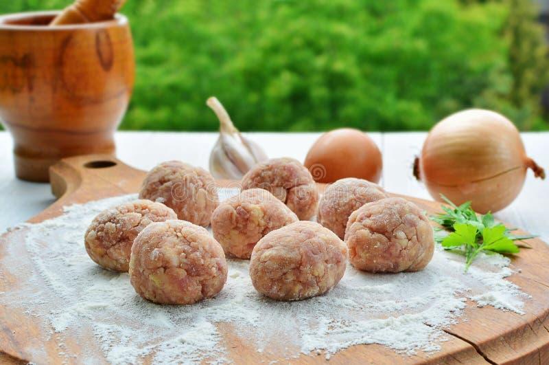 Rå köttbullar med ingredienser som är klara att stekas royaltyfria foton
