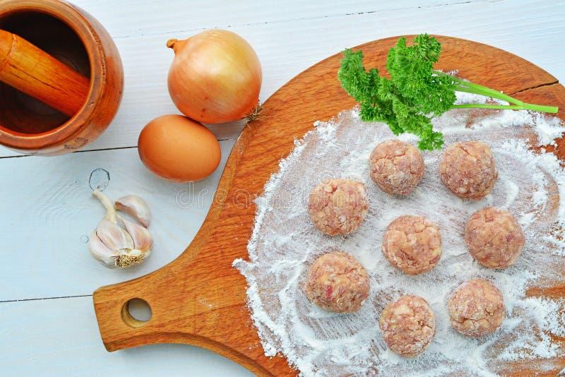 Rå köttbullar med ingredienser som är klara att stekas arkivfoto