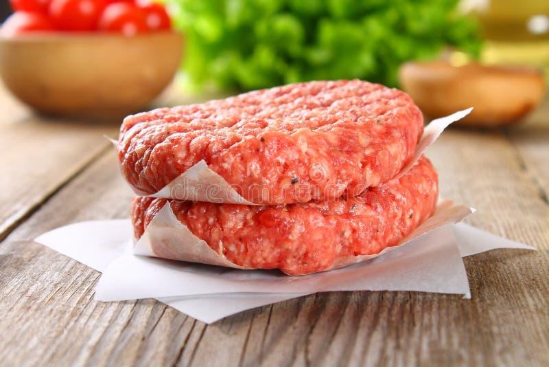 Rå köttfärs för hem gjorde gallerhamburgare som lagar mat med utrymmen och örter royaltyfri bild