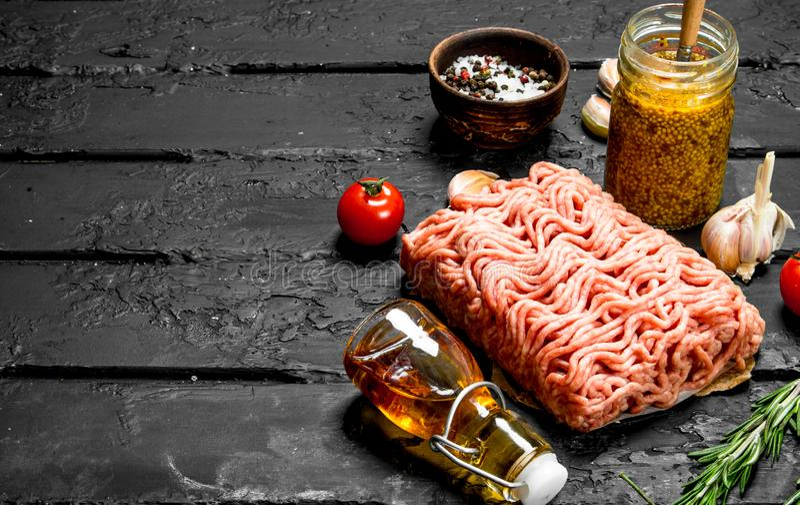 Rå köttfärs med kryddor och kruset av senap arkivfoto