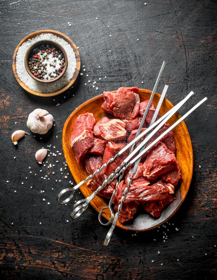 Rå kebab på en platta med steknålar, kryddor och vitlök royaltyfri bild