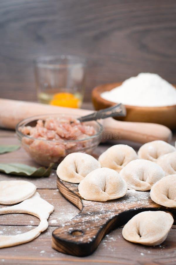 Rå klimpar på skärbrädan och ingredienser för deras förberedelse: mjöl ägg, köttfärs royaltyfria bilder