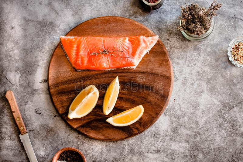 Rå läcker laxbiff Peppra, salta, fred av citronen och rosmarin på ett träbräde Sund mat, bantar eller matlagningbegreppet royaltyfri bild