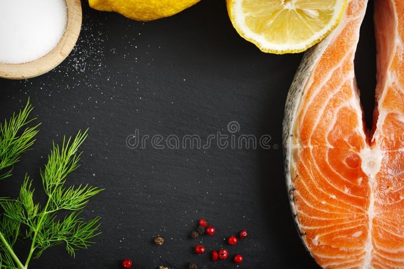 Rå laxbiff med örter och citronen på svart bräde royaltyfri bild