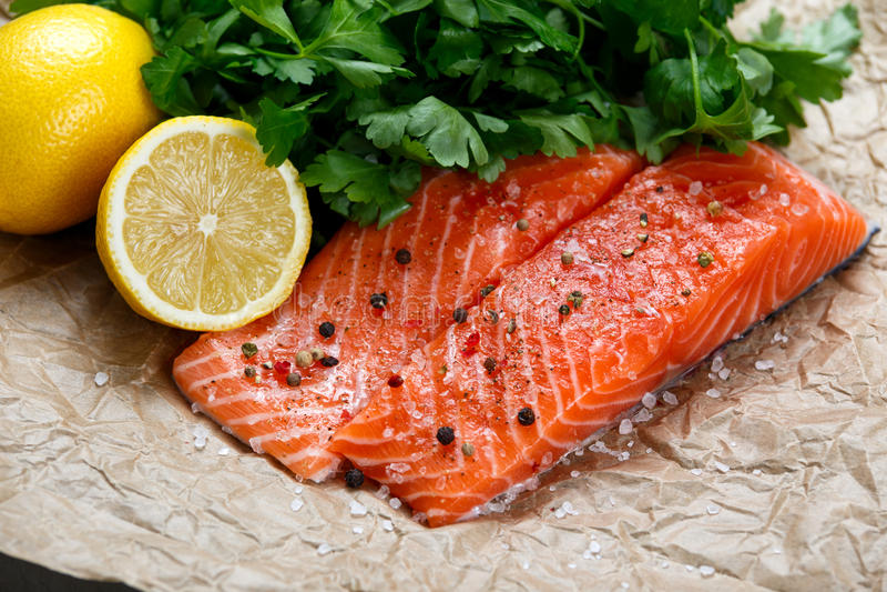 Rå laxfiskfilé med nya örter på skrynkligt papper royaltyfria bilder