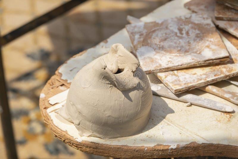 Rå lera för krukmakeri som modellerar med en spackel och gjuter hjälpmedel Utomhus- krukmakeriworkspace för sommar arkivbild