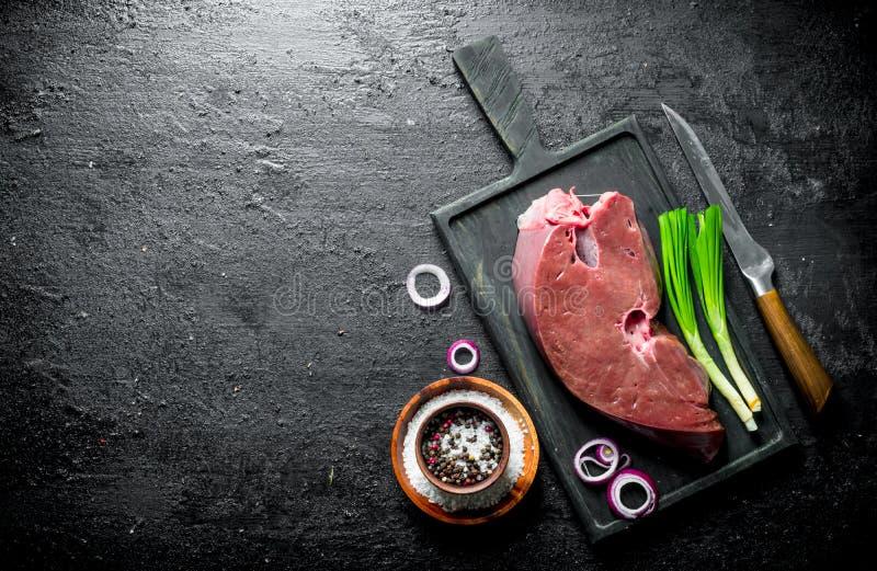 Rå lever med kryddor och salladslöken royaltyfri fotografi
