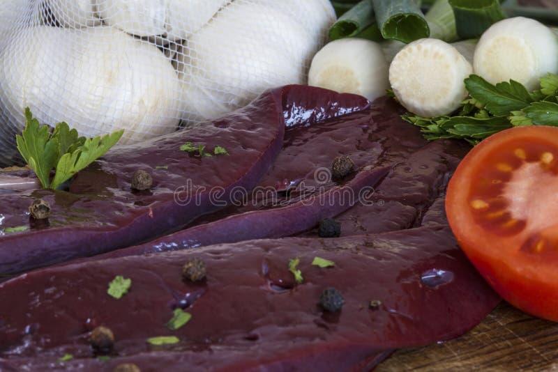 Rå lever med vitlöklökar och tomater arkivbild