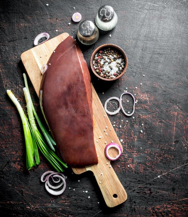 Rå lever på en skärbräda med salladslökar, kryddor och lökcirklar royaltyfri bild