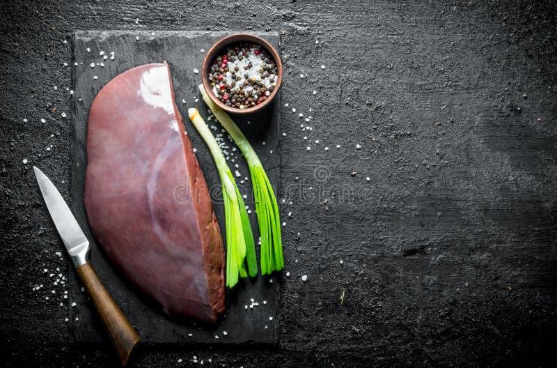 Rå lever på ett stenbräde med salladslökar och kryddor royaltyfri fotografi