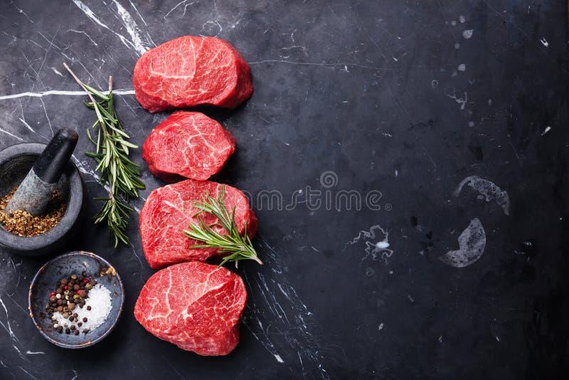 Rå marmorerad köttbiff och smaktillsatser royaltyfri bild
