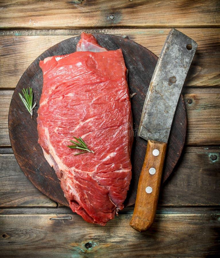 rå meat Ett stycke av nytt nötkött med en handyxa på en gammal skärbräda rå meat royaltyfri foto
