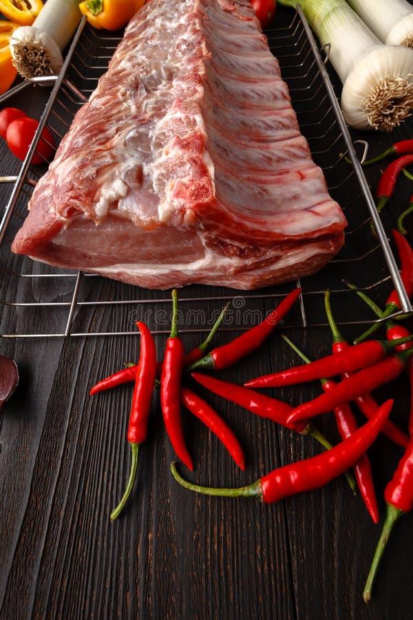 rå meat Rå nötköttbiff på en skärbräda med örter och veget royaltyfri fotografi