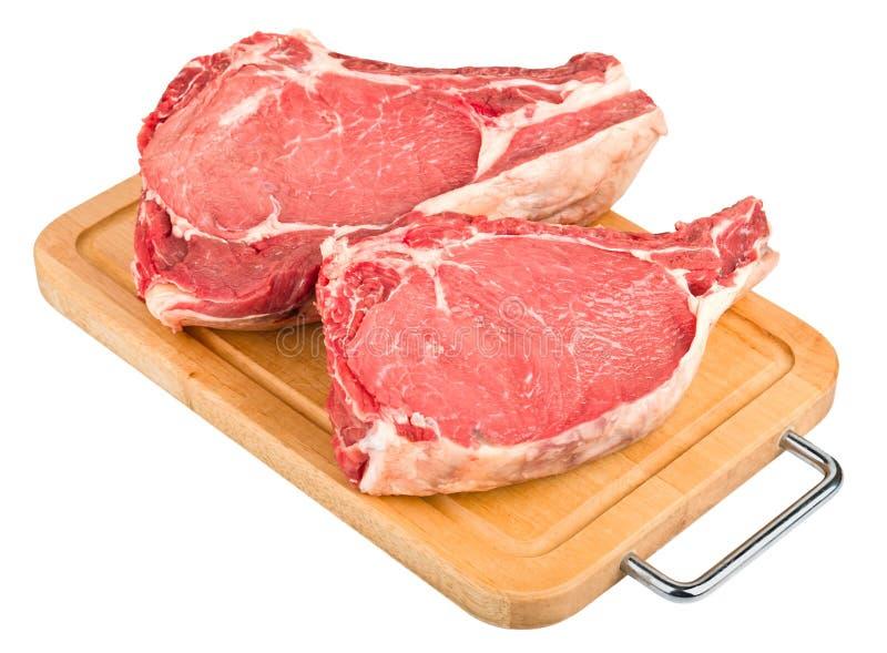 Rå meat på det wood brädet fotografering för bildbyråer