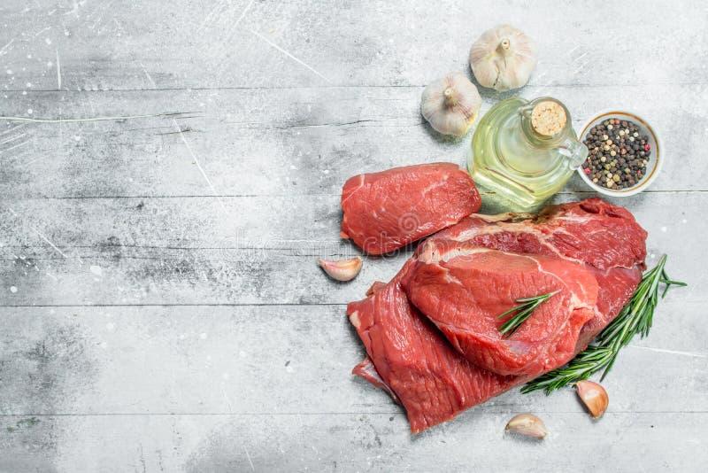 rå meat Stycken av nötkött med vitlök, rosmarin och olivolja royaltyfri bild