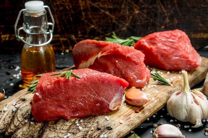 rå meat Stycken av nytt nötkött med kryddor, vitlök och rosmarin arkivfoto