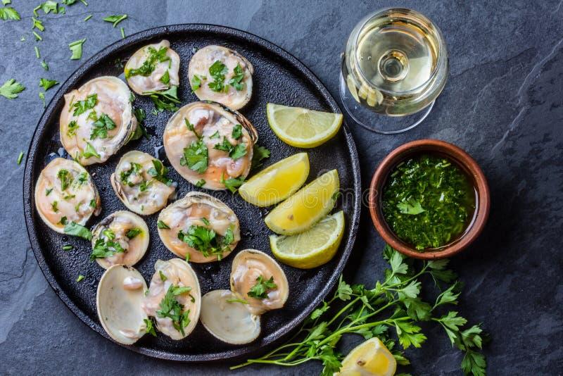 Rå musslor med citronen, örter och vitt vin, kritiserar bakgrund arkivfoton