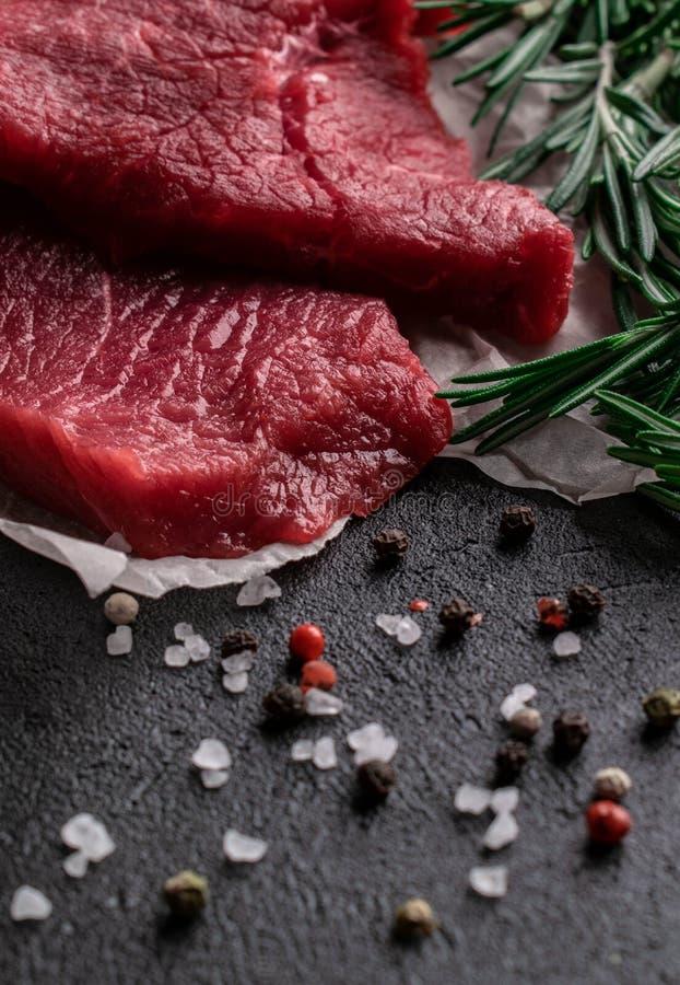 Rå nötköttbiff med rosmarinfilialer på pergamentpapper med peppar och att salta arkivbild