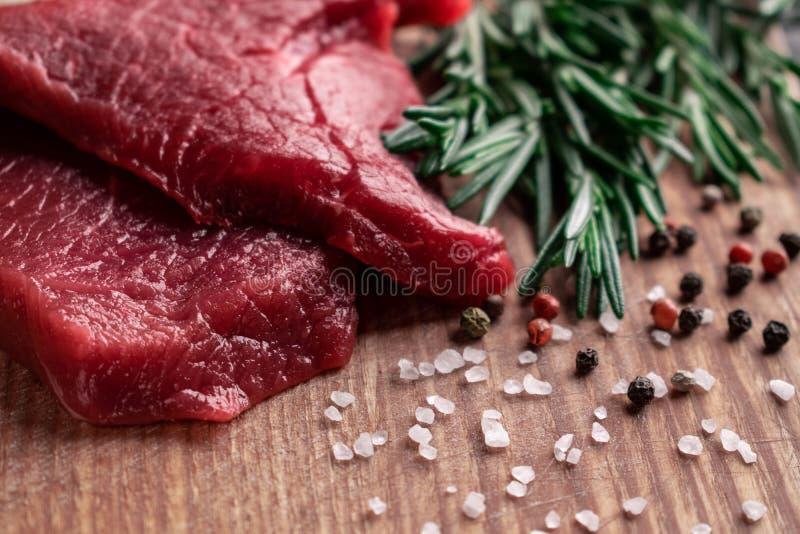 Rå nötköttbiff med rosmarinsvart, röd peppar och det grova havet saltar royaltyfria bilder