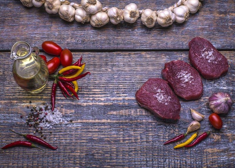 Rå nötköttbiffar som är klara för att grilla som är salta, peppar, tomater, vitlök, extra jungfrulig olivolja på träbakgrund över royaltyfria bilder