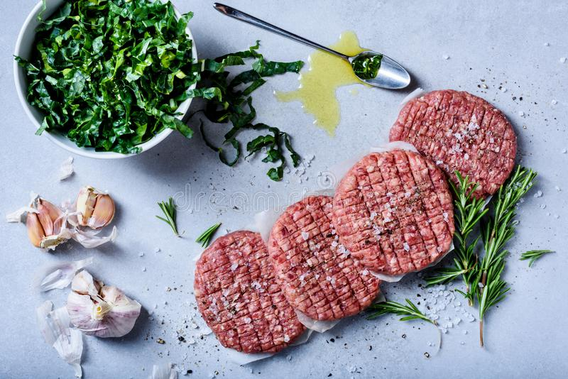 Rå nötkötthamburgaresmå pastejer med sallad, sund matlagning arkivbilder
