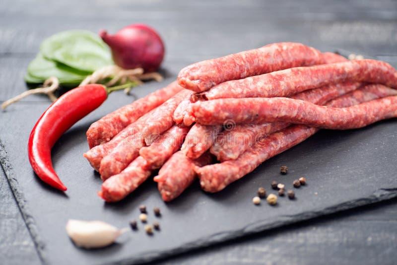 Rå nötköttkorvar, kyligt och spenat stock illustrationer