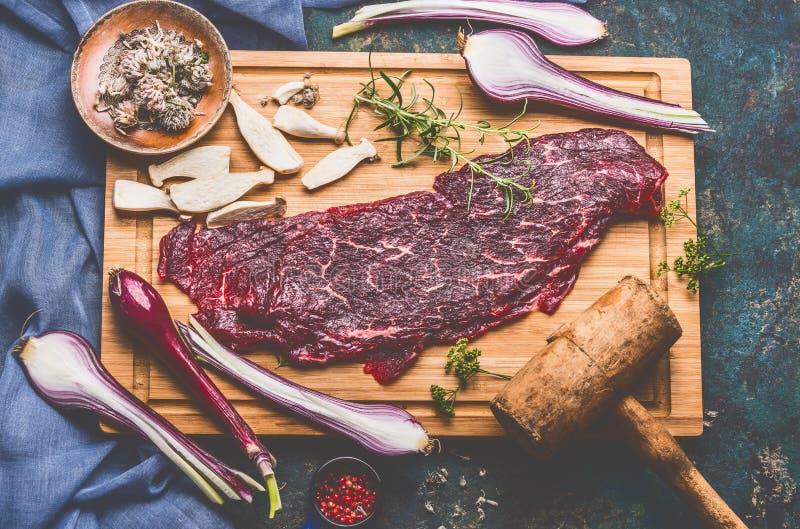 Rå nötköttkotlett med träkötttenderizer- och matlagningingredienser på skärbräda royaltyfria bilder
