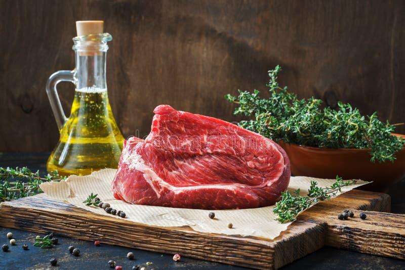 Rå nötköttmarmorfläskkarré Rå nötköttfilé på en lantlig tabell med timjan och olivolja arkivbilder