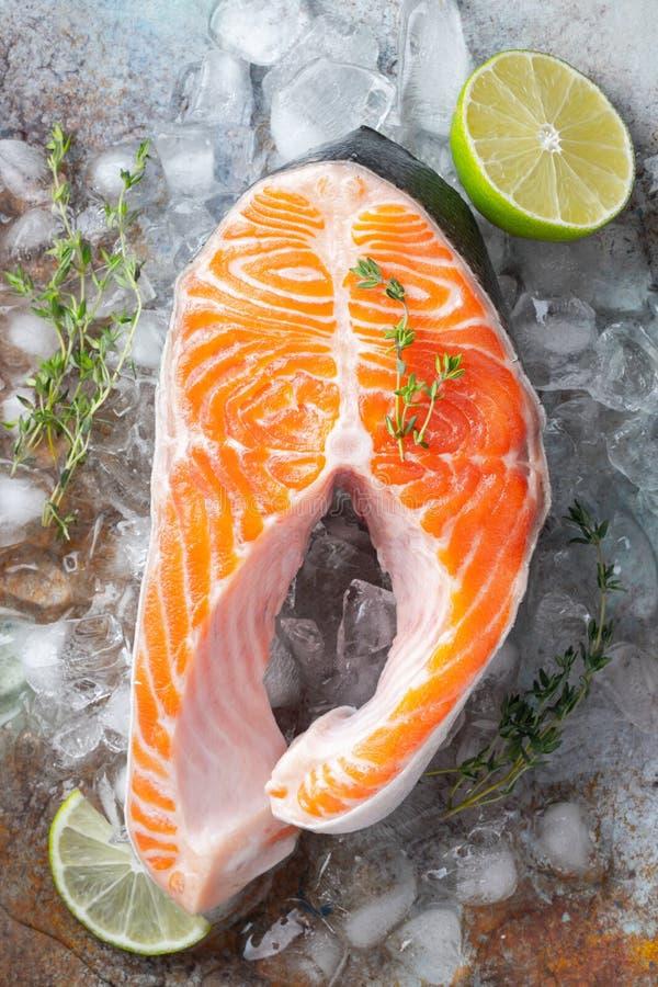 Rå ny lax- eller forellbiff på is som, är rik i olja omega-3, med limefrukt, timjan och olivolja på en blå rostig bakgrund Sunt royaltyfria foton