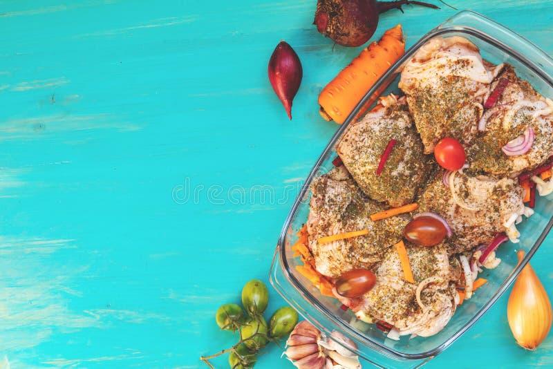 Rå nya fega lår med kryddor och grönsaker i ett exponeringsglas b arkivfoton