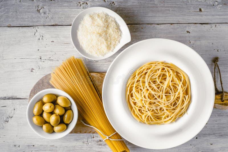 Rå och lagad mat spagetti med oliv och ost på den vita träbästa sikten för tabell Begrepp av italiensk kokkonst royaltyfri bild